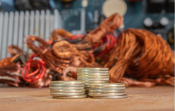 Stack of coins in front of copper showing the incentive to scrap copper